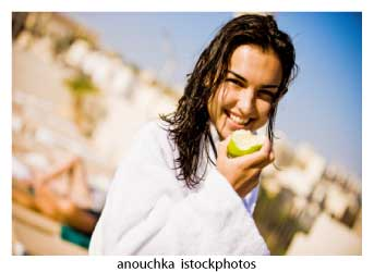 woman in white robe eating an apple at weigh loss spa