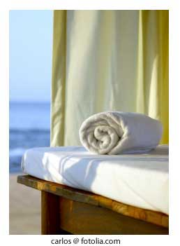 rolled towel on massage table on a caribbean beach