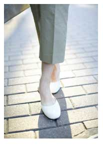 woman's lower legs with grey pants and white shoe