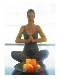 woman sitting in lotus pose with a tray of candles before her